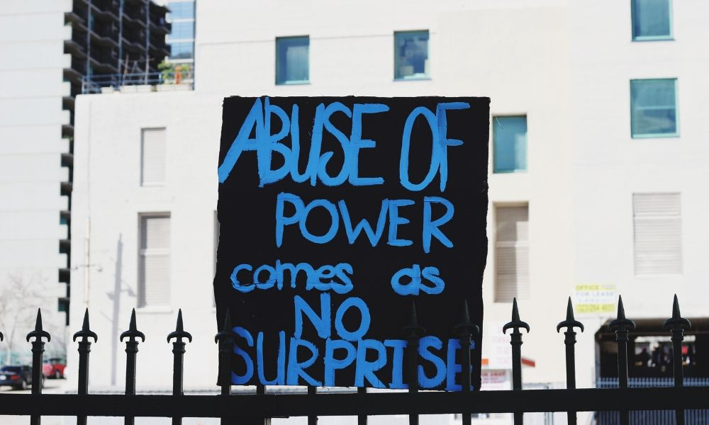 """Sign reading """"abuse of power comes as no surprise"""""""