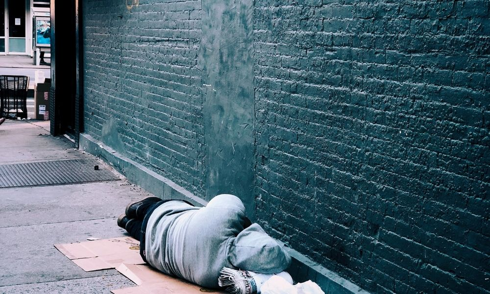 Homeless person laying on street against a brick wall