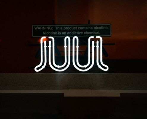 Jul sign blowing neon with a warning about nicotine above it