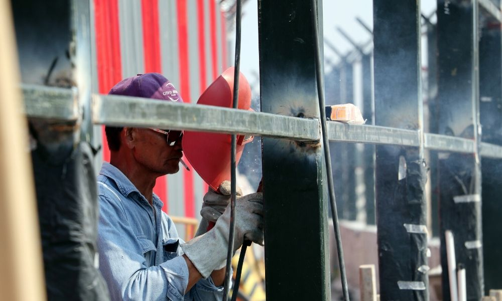 man welding with mask pulled back