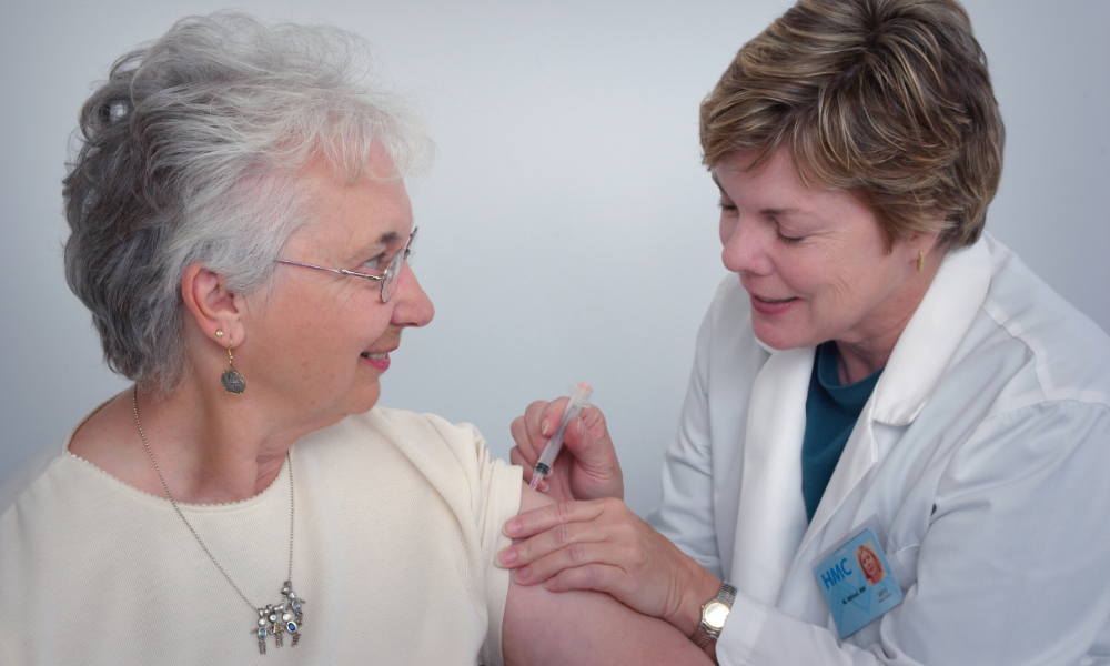 Nurse gives elderly patient a shot
