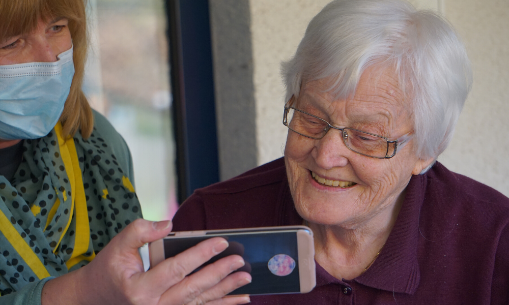 nurse showing a patient a cell phone picture in nursing home