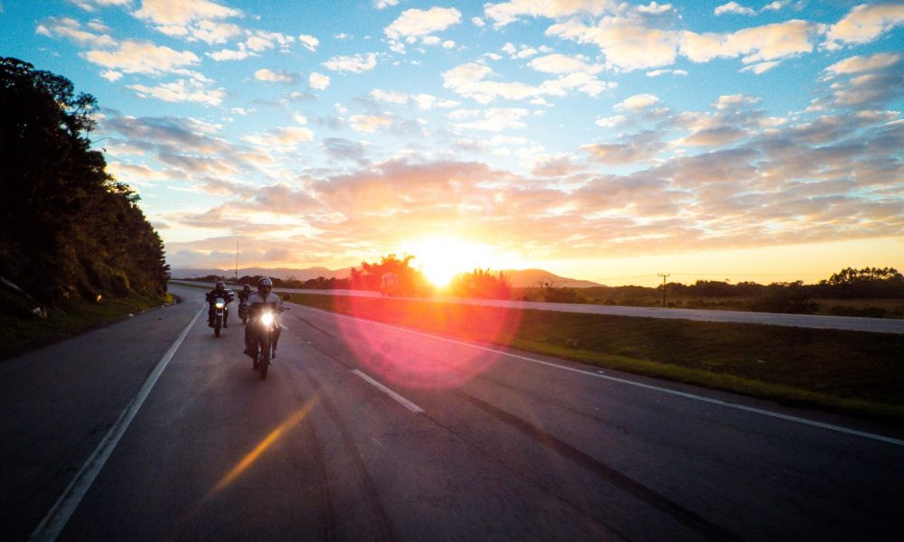 two motorcycles driving fast during a sunset
