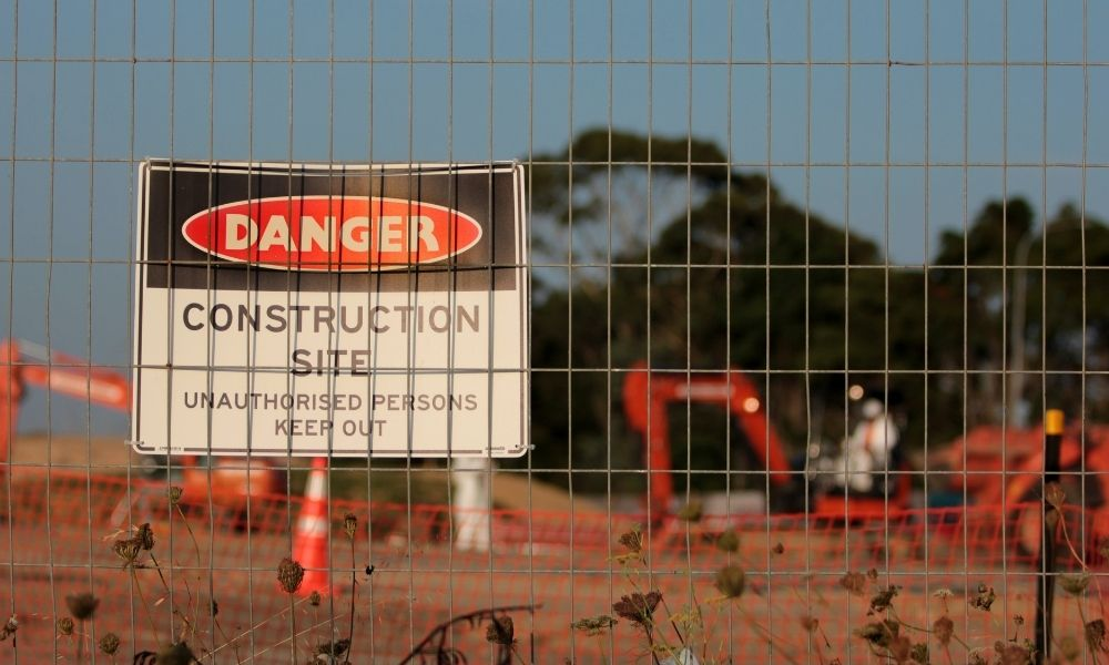 sign reading danger construction posted behind a fence