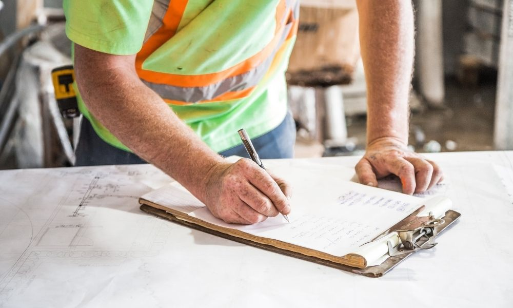 construction worker filling out paperwork on a clipboard