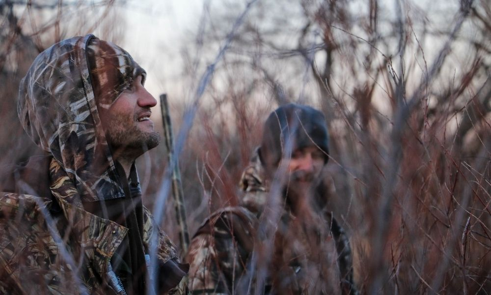 two hunters share a laugh while camouflaged